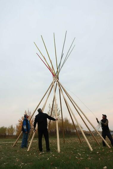 Three adult men setting up tipi poles outdoors